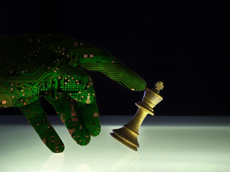 Die Hand von einem Roboter stößt eine Schachfigur um.